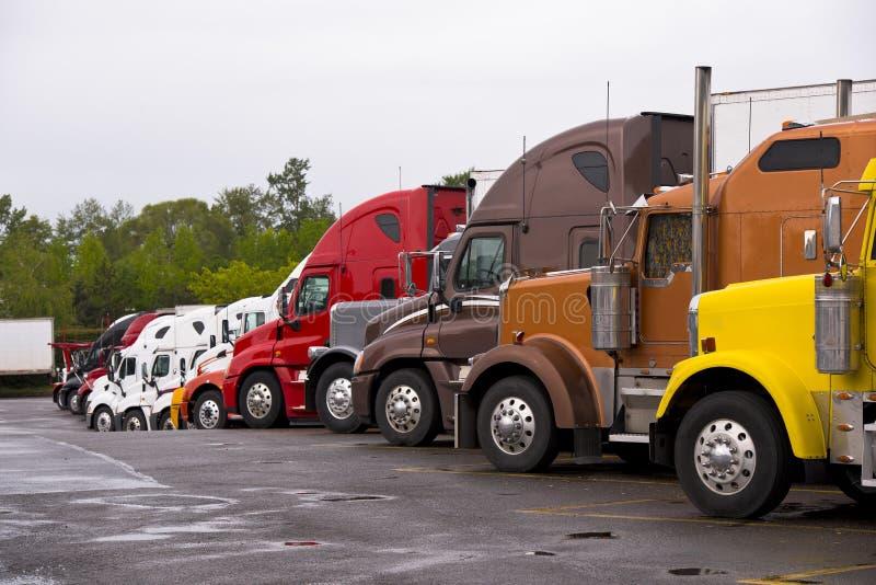 Camiones coloridos de la procesión en la parada de camiones después de la lluvia fotos de archivo