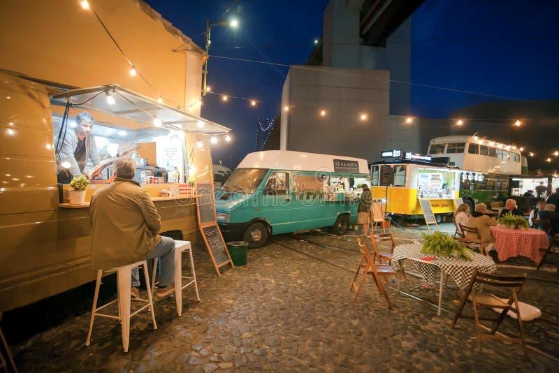 Camiones de los alimentos de preparación rápida parqueados en la zona urbana y la gente hambrienta que cenan último al aire libre imágenes de archivo libres de regalías
