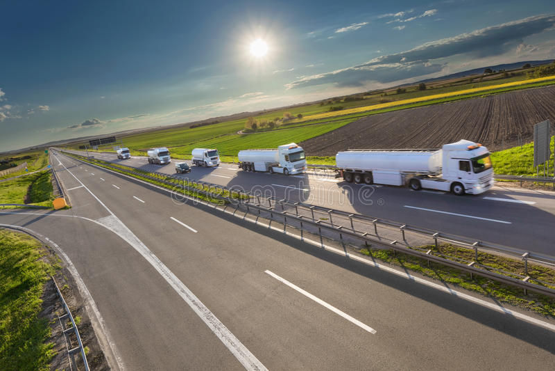 Camiones del tanque en la conducción izquierda en la carretera en el día soleado fotos de archivo