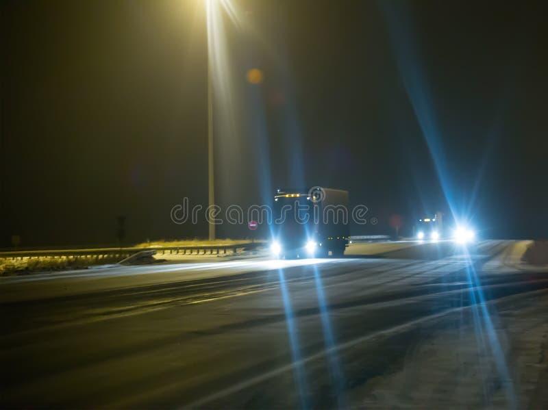 camiones en el camino nevoso del invierno de la noche imagen de archivo
