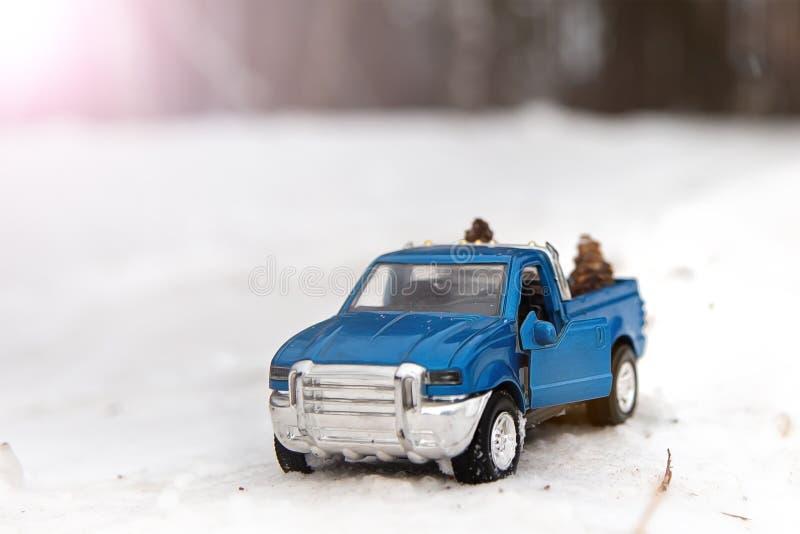 Camioneta pickup azul del juguete en bosque del invierno en el camino con la puerta abierta imagen de archivo libre de regalías