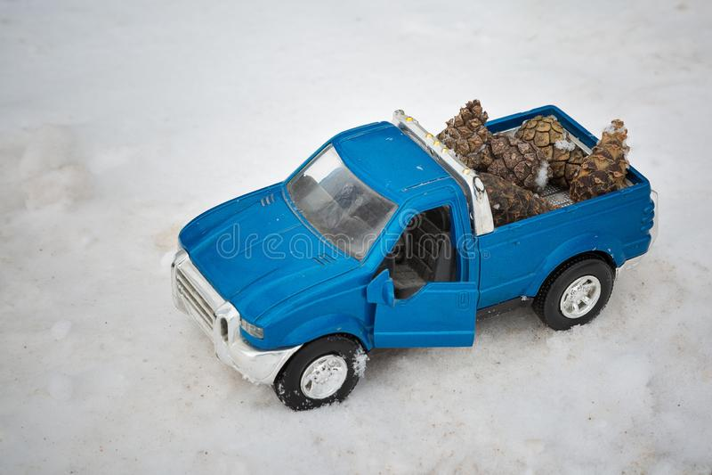 Camioneta pickup azul del juguete en bosque del invierno en el camino con la puerta abierta Conos de abeto que llevan en la parte foto de archivo