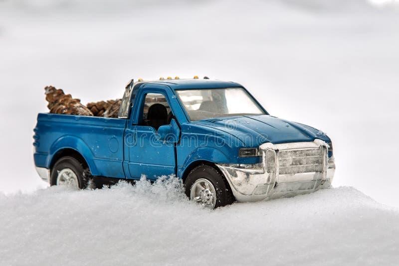 Camioneta pickup azul del juguete en nieve Pegado en la nieve acumulada por la ventisca Conos de abeto que llevan en la parte pos fotografía de archivo