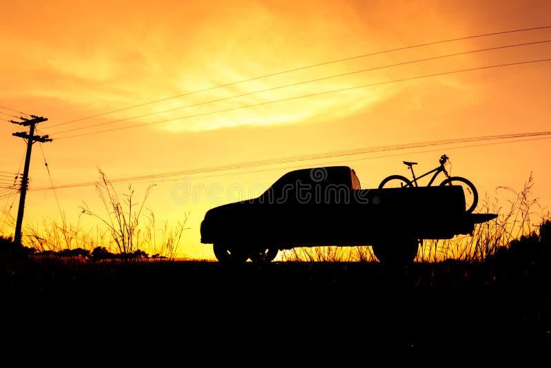 Camioneta pickup de la silueta con la bicicleta imagenes de archivo