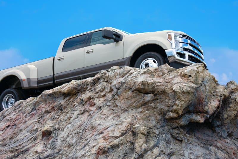 Camionete áspero grande que conduz em uma borda rochosa do penhasco fotografia de stock