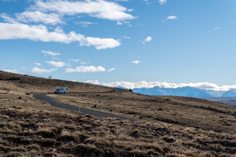 Camionete de campista que conduz abaixo da estrada da montanha em Nova Zelândia foto de stock