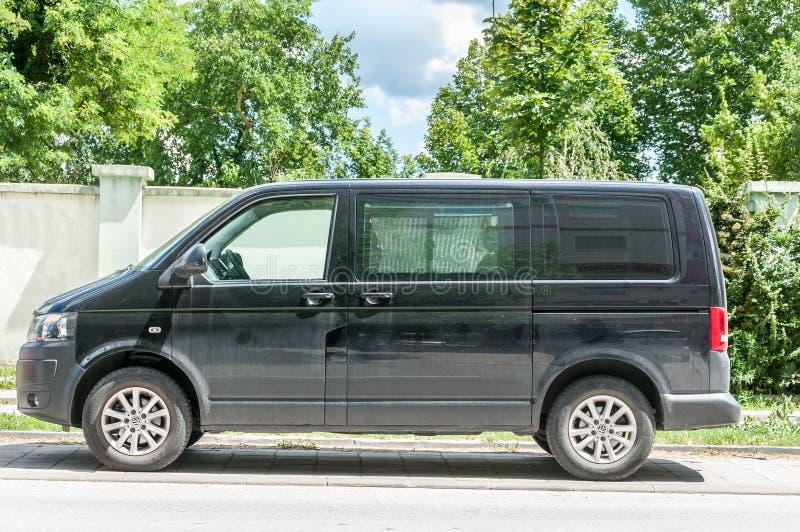 A camionete de passageiro preta do transportador de Volkswagen T 5 estacionou na rua imagens de stock