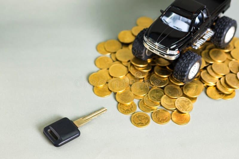 Camionete diminuto chave do carro do carro em pilhas de moedas em vagabundos cinzentos imagem de stock royalty free