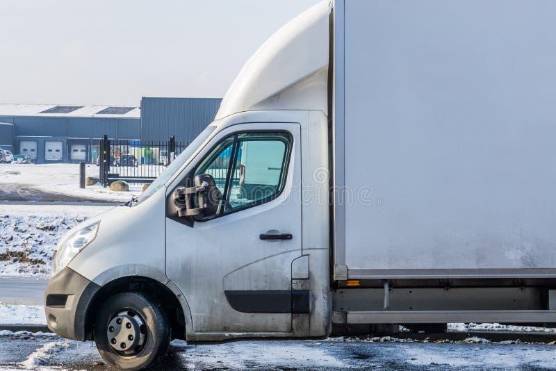 Camionete estacionada branca durante o inverno com um armazém no veículo do fundo, da logística e do transporte fotografia de stock