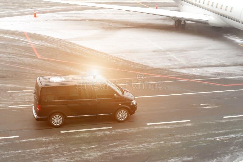 Camionete preta do serviço do VIP que corre no taxiway do aeroporto com o jato privado borrado no fundo Serviço da classe executi imagens de stock royalty free