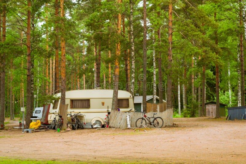 Camionetes e bicicletas de acampamento em acampamento arborizado Hamina, Finlandia, Suom fotos de stock royalty free