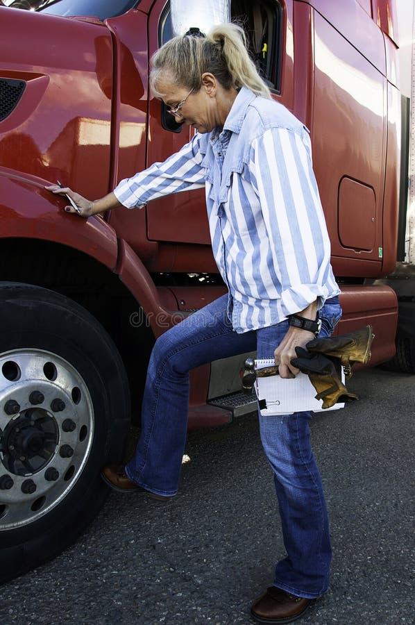 Camionista da mulher que faz uma inspeção completa do caminhão fotos de stock royalty free
