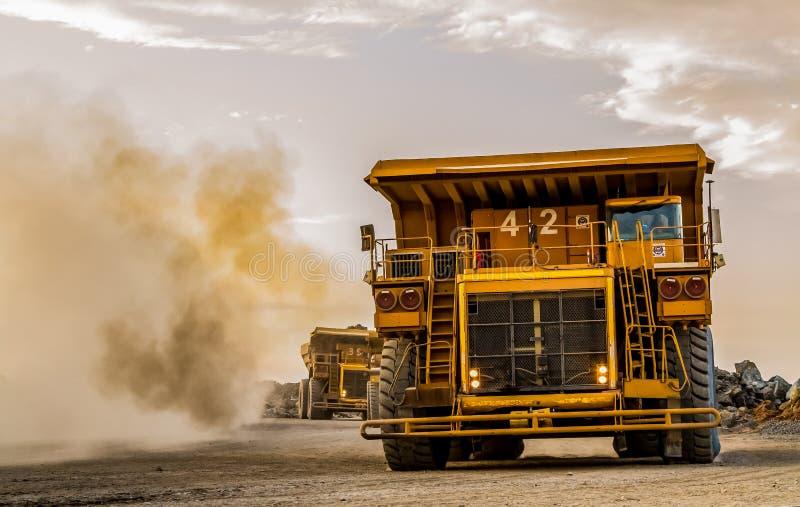 Camions à benne basculante d'exploitation transportant le minerai de platine pour le traitement photographie stock