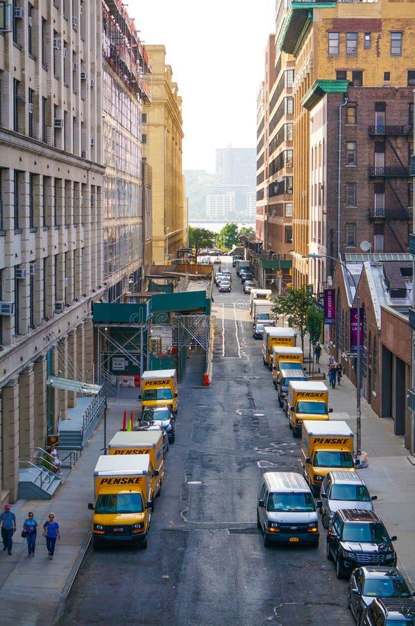 """Camions """"Penske """"dans une rangée dans la rue étroite de NYC avec des personnes marchant par images libres de droits"""