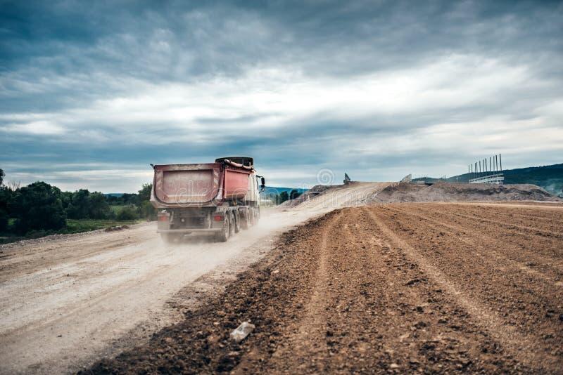 camions de déchargeur travaillant au chantier de construction de route, chargement et déchargeant le gravier et la terre activi r images stock