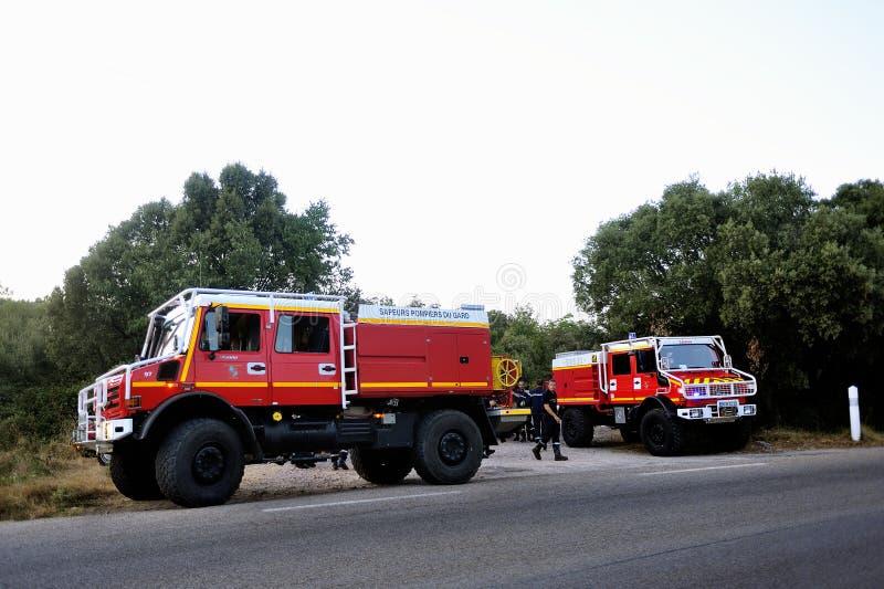 Camions de pompiers à l'entrée d'un chemin forestier images stock