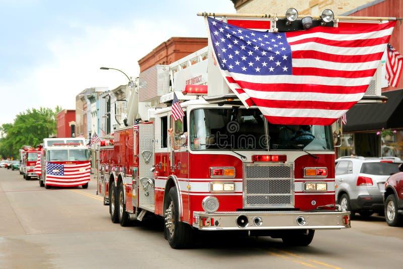 Camions de pompiers avec les drapeaux américains au défilé de petite ville images libres de droits