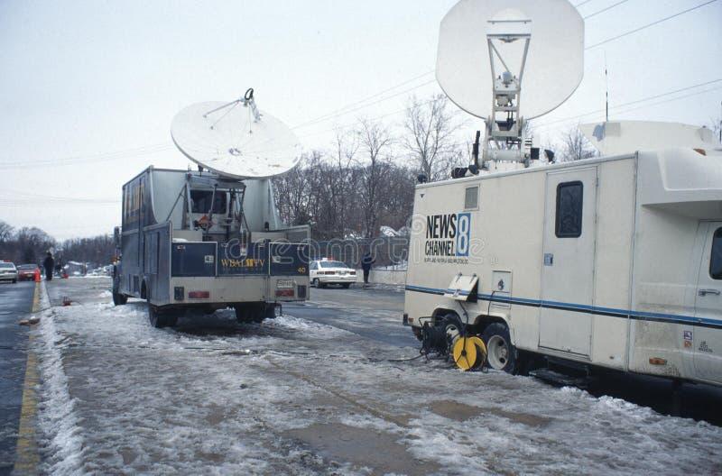 Camions satellites de TV sur un pont donnant sur une épave de train photographie stock