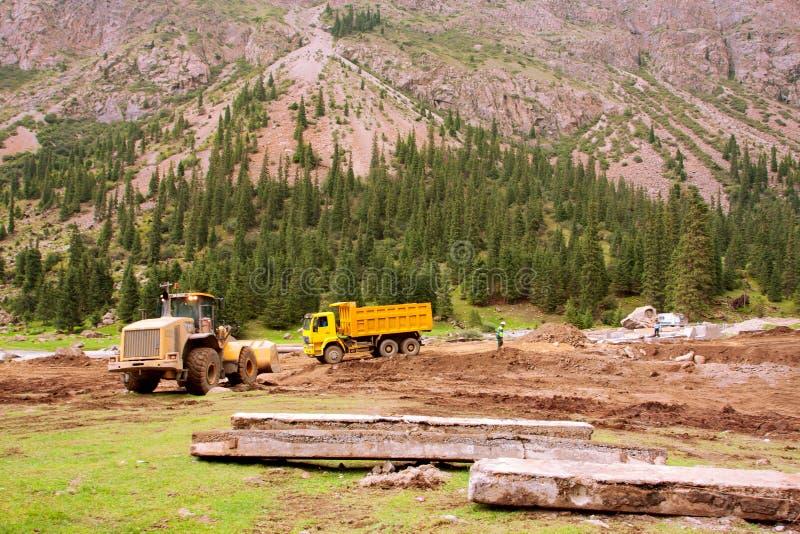 Camions sur la route pendant les réparations après inondation dans une vallée entre les montagnes de l'Asie centrale images libres de droits