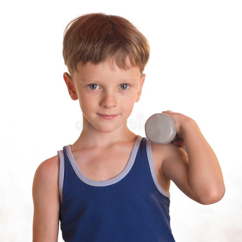 Camisa azul del muchacho que hace ejercicios con pesas de gimnasia sobre el backgro blanco fotos de archivo