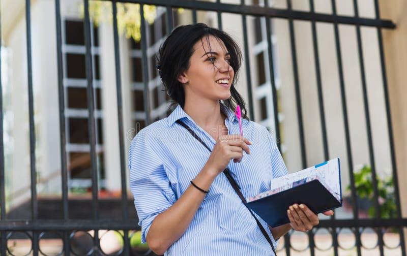 Camisa azul que lleva femenina de la morenita feliz hermosa caucásica alegre, haciendo notas en libreta mientras que camina al ai imagenes de archivo