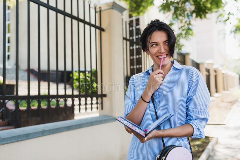 Camisa azul que lleva femenina encantadora de la morenita feliz hermosa caucásica, haciendo notas en libreta mientras que camina  imagen de archivo