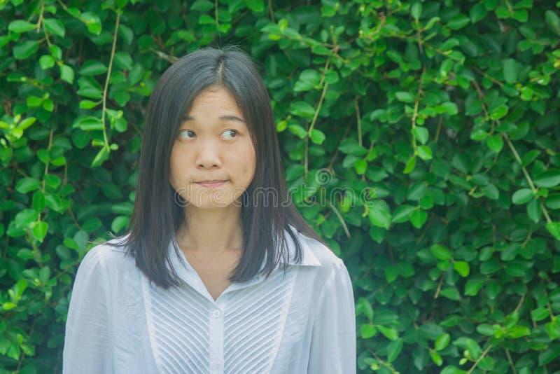 Camisa blanca de la mujer de la foto del lanzamiento del desgaste asiático del retrato, pensando y mirando de lado con el fondo v fotografía de archivo libre de regalías