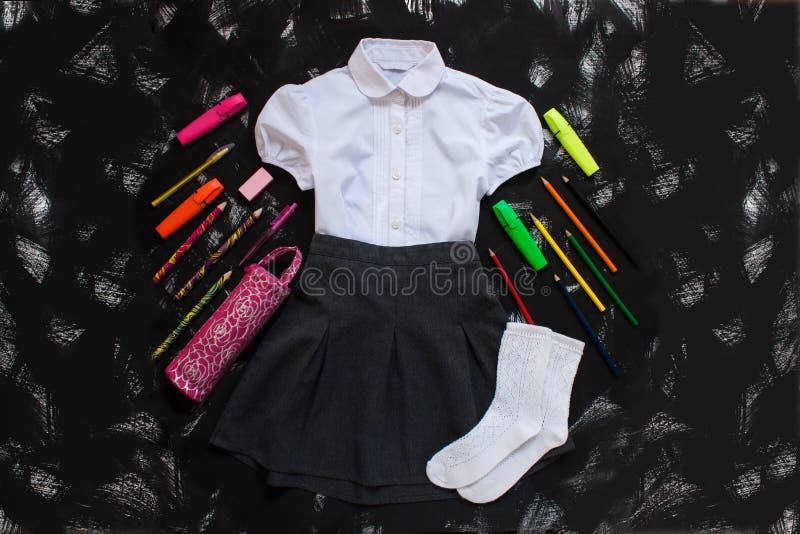 Camisa blanca, falda gris y fuentes de los efectos de escritorio en fondo negro Primer de septiembre, nuevo año escolar imagen de archivo libre de regalías