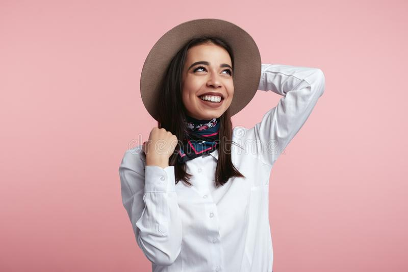 Camisa blanca que lleva de la chica joven de moda y bufanda elegante, sosteniendo sombrero y mirando lejos sobre la pared rosada  foto de archivo
