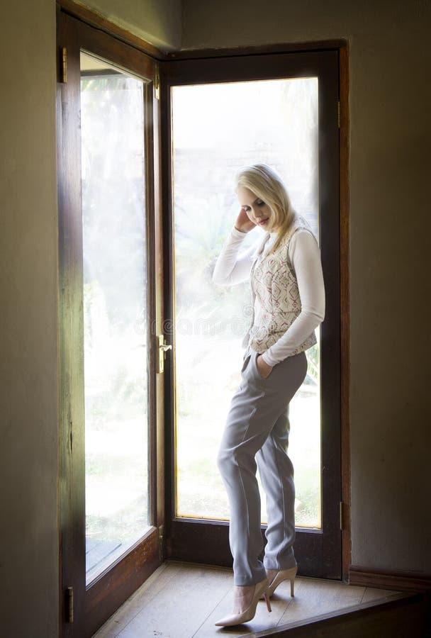 Camisa blanca que lleva de la mujer rubia sofisticada, pantalones grises, talones y bufanda, presentando al lado de las puertas d fotos de archivo