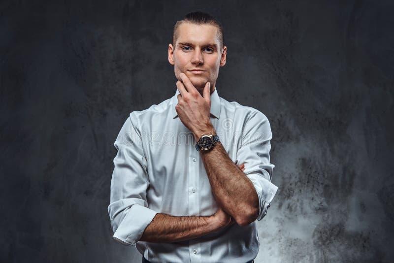 Camisa blanca que lleva elegante vestida y corbata de lazo confiadas del hombre, tocando su cara y mirando una cámara fotografía de archivo libre de regalías