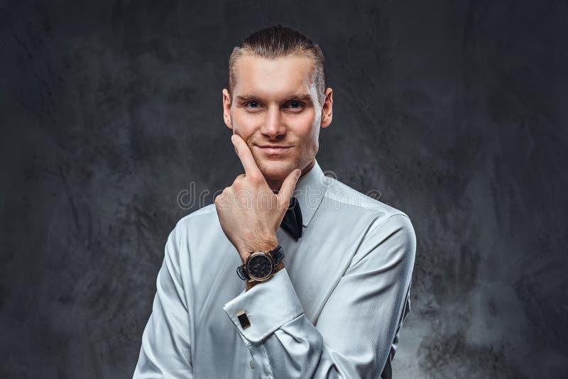 Camisa blanca que lleva elegante vestida y corbata de lazo confiadas del hombre, tocando su cara y mirando una cámara imagen de archivo