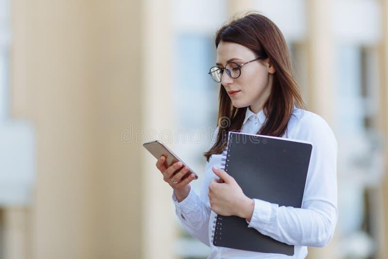 Camisa blanca que lleva joven de la mujer de negocios del retrato usando puertas del smartphone hacia fuera Mensaje de lectura fe foto de archivo libre de regalías