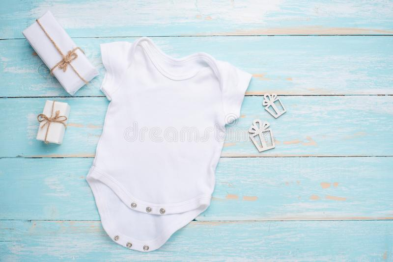 Camisa branca do bebê da configuração lisa do modelo com presentes em um fundo azul Disposição para o projeto e a colocação dos l fotografia de stock