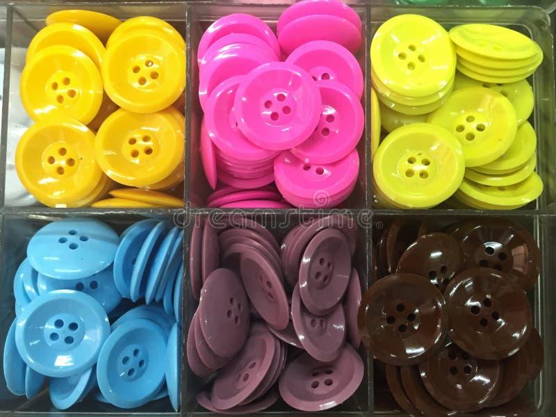 Camisa colorida del botón en caja plástica foto de archivo
