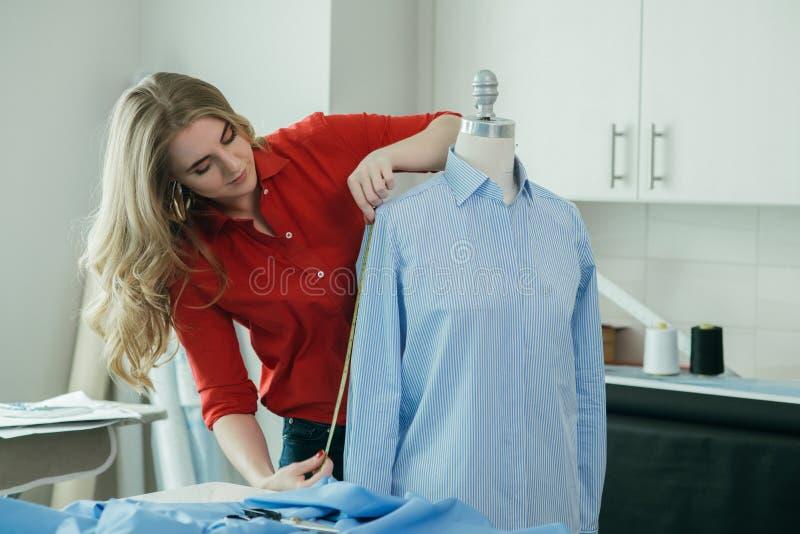 Camisa de medição da mulher do alfaiate em um manequim com linha de medição na oficina fotografia de stock royalty free