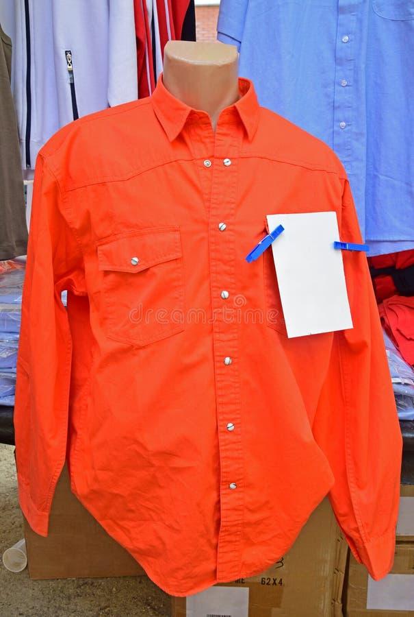 Camisa larga anaranjada del trabajo de la manga en la exhibición en mercado del fin de semana foto de archivo libre de regalías