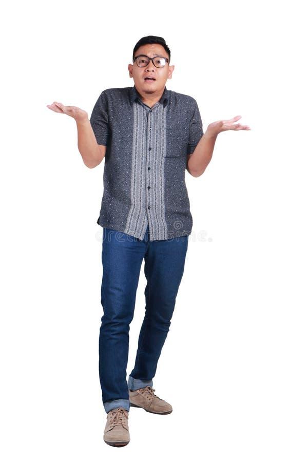 Camisa permanente del batik del hombre que lleva asiático joven, gesto del encogimiento de hombros fotos de archivo