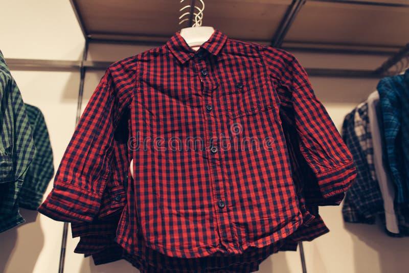 A camisa quadriculado vermelha das crianças no trempel na loja de roupa das crianças no shopping imagens de stock royalty free