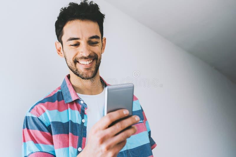 Camisa que lleva del hombre caucásico feliz, mandando un SMS en el teléfono móvil, presentando contra el For Your Information bla fotografía de archivo