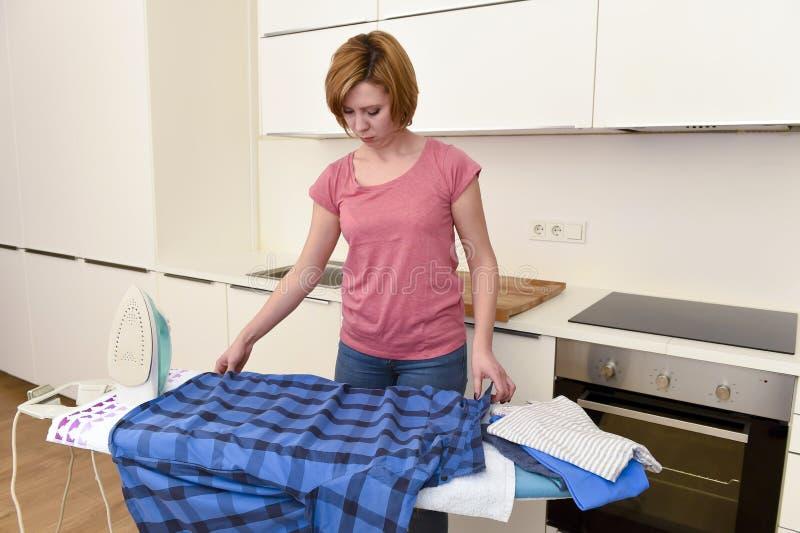 Camisa que plancha de la mujer hermosa o del ama de casa eficiente cuidadosamente imagenes de archivo