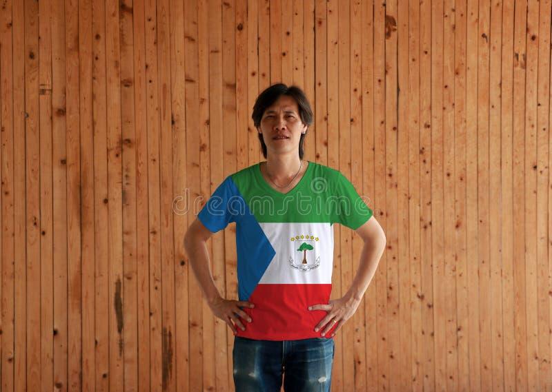 Camisa vestindo da cor da bandeira da Guiné Equatorial do homem e estar com o akimbo no fundo de madeira da parede imagens de stock