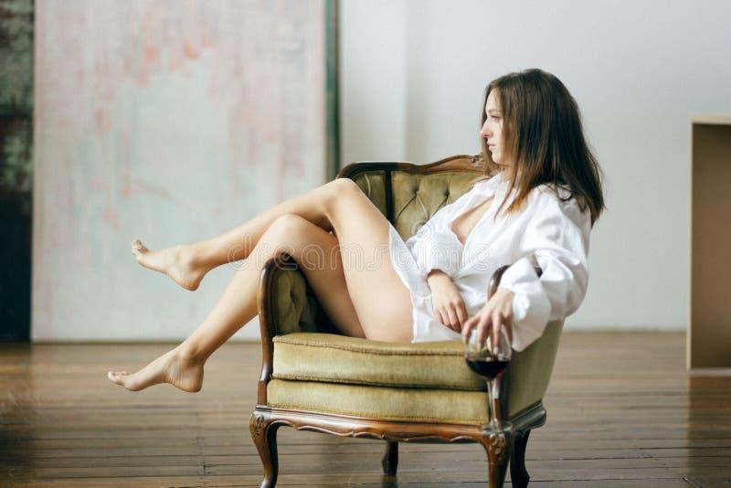 Camisa vestindo do ` s dos homens brancos da menina bonita impar nova com a cara pensativa sensual que senta-se na cadeira, guard foto de stock royalty free