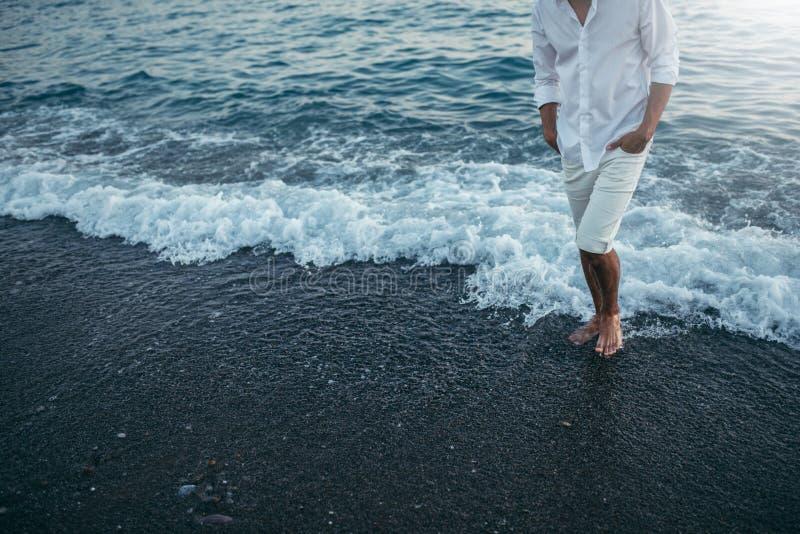 Camisa y pantalones blancos que llevan cosechados atractivos del cuerpo del hombre en foto de archivo libre de regalías