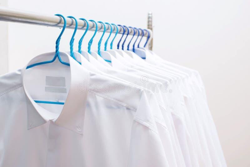 Camisas blancas que cuelgan en el estante en fila imagen de archivo