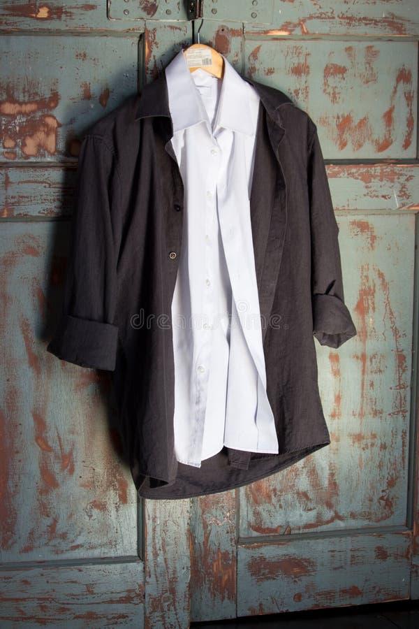 Camisas brancas e pretas no gancho contra a porta de madeira do grunge Roupa masculina e conceito da forma Os homens formam no es foto de stock royalty free