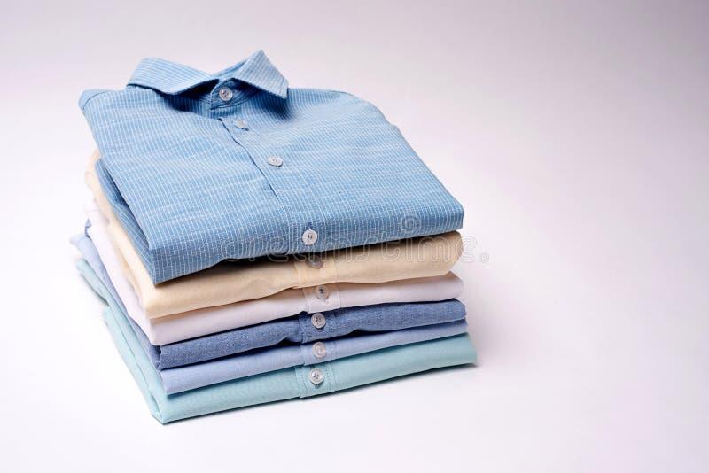 Camisas clássicas do ` s dos homens empilhadas no fundo branco fotografia de stock