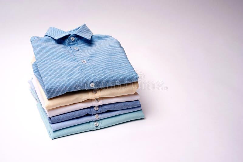 Camisas clássicas do ` s dos homens empilhadas no fundo branco foto de stock royalty free