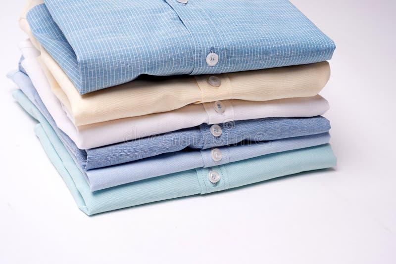 Camisas clássicas do ` s dos homens empilhadas no fundo branco imagens de stock royalty free