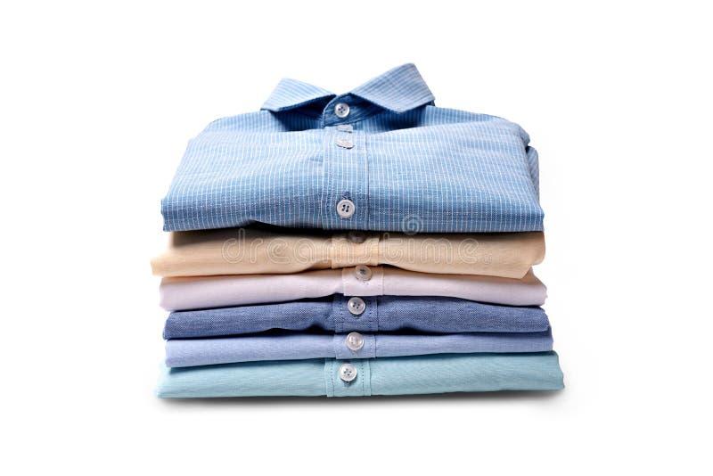 Camisas clássicas do ` s dos homens empilhadas no fundo branco fotos de stock